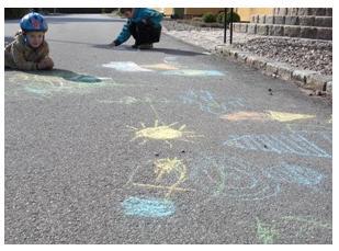 Barn målar med ekologiska gatukritor