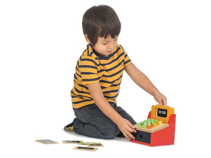 Barn som leker med kassaapparat