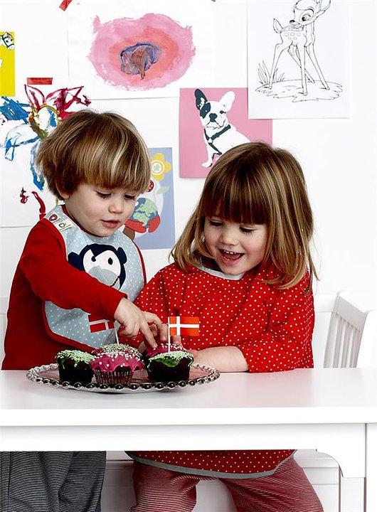 Barn med barnförkläde som äter kakor