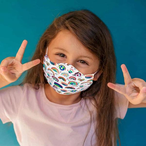 Barn med munskydd med regnbågar på