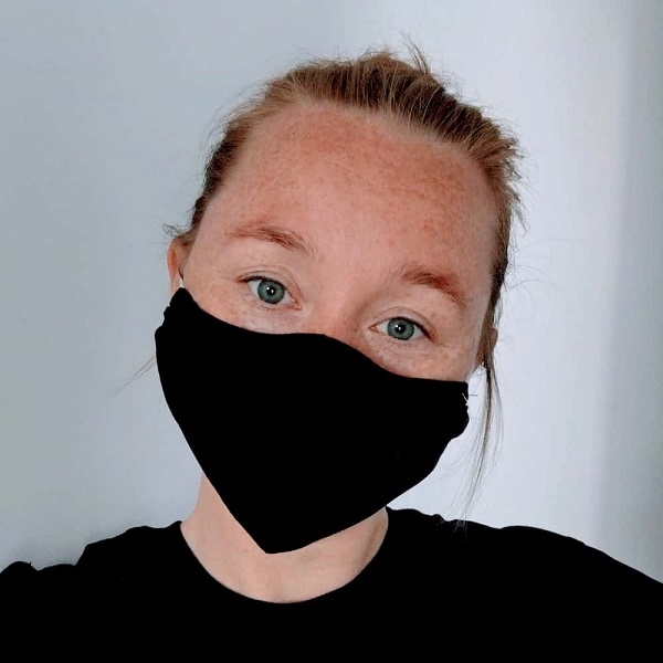 Kvinna med svart munskydd på sig